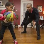 Adult and Child Play Basketball in a living room