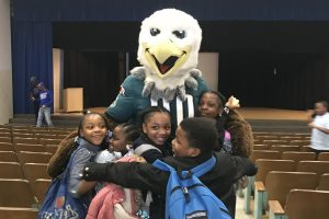 Prince Hall students hugging Swoop mascot