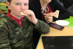 Student eating mushroom quesadillas with Dayle Hayes