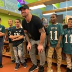 Students taking pictures at Eagles Book mobile with Eagles player Chris Long